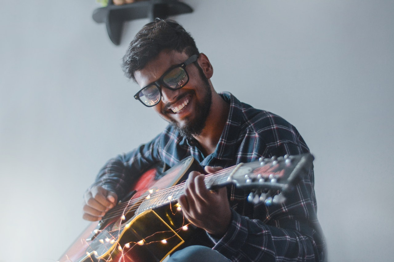 man smiling while playing guitar