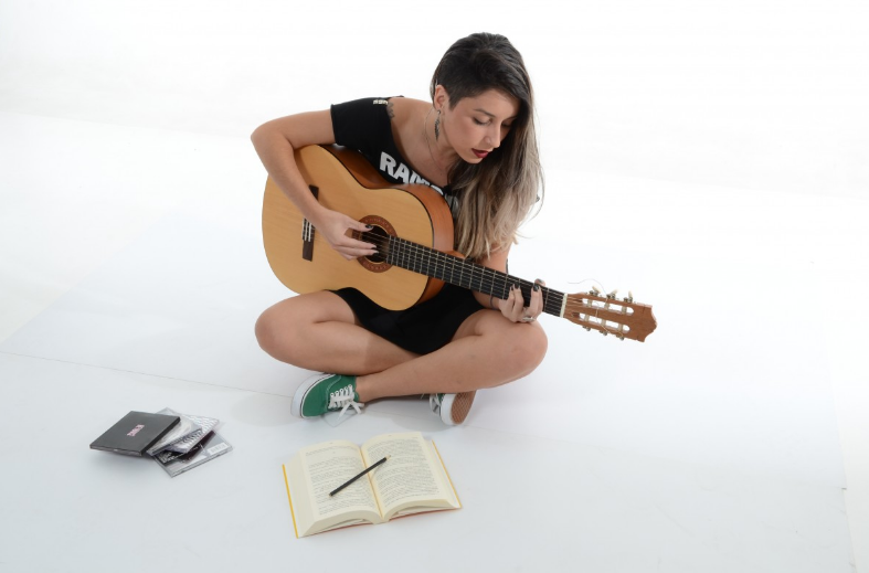 woman wearing black shirt playing guitar