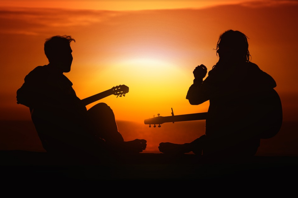 silhouette of the two man playing guitar during sunset