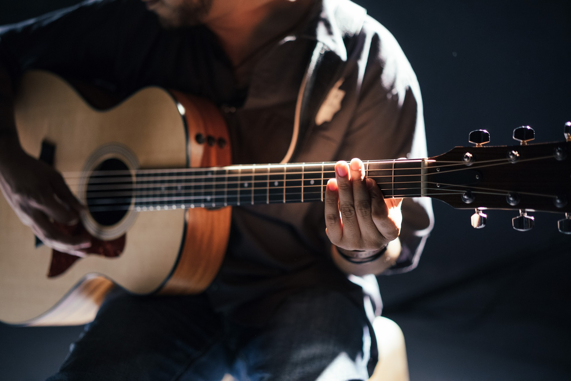 A person is holding a guitar and harmonizing it using the open d tuning